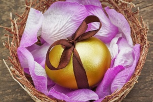 Easter golden egg with brown ribbon in a nest on a wooden textur